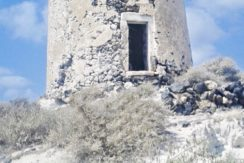 Windmill in Santorini with caves 4